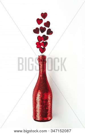 Vibrant red heart-shaped confetti poured out of champagne bottle in cover spangled with vibrant red sequines on white background. Mockup for your design. Creative trendy flat lay with space for text. Love and celebration concept. stock photo