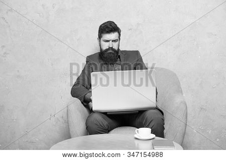 Getting business information surfing the Internet. Businessman making Internet project at laptop. Bearded man using mobile Internet connection. The Internet is the great equalizer in business. stock photo