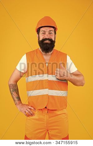 Good job. Safety apparel for construction industry. Bearded brutal hipster safety engineer. Man engineer protective uniform orange background. Engineering career concept. Architect builder engineer. stock photo