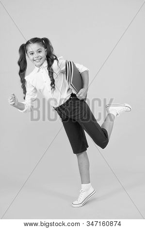 Hurry up. Girl with books on way to school. Knowledge day. Back to school. Kid cheerful schoolgirl running. Pupil want study. Active child in motion. Beginning school lesson. Keep going. Active kid. stock photo