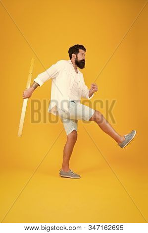 Knowledge in brutal world. Brutal hipster walking with ruler on yellow background. Bearded man with brutal look going to school. Brutal caucasian guy back to school and looking cool. stock photo