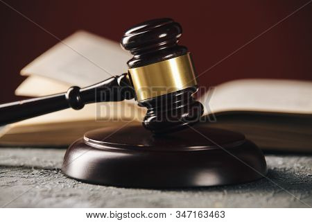 Law concept - Open law book with a wooden judges gavel on table in a courtroom or law enforcement stock photo