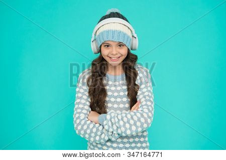 musical suggestions for playlist. winter music activity. happy girl enjoy winter playlist. music mood. little child knitted sweater and hat. kid blue background. songs about winter. Winter fun. stock photo