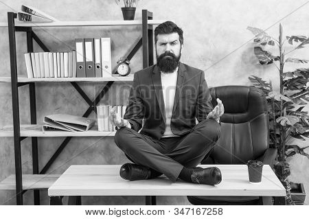 Prevent professional burnout. Way to relax. Meditation yoga. Self care. Psychological help. Relaxation techniques. Mental wellbeing and relax. Man bearded manager formal suit sit lotus pose relaxing. stock photo