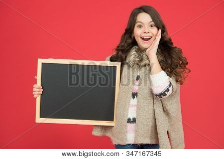 Profitable deal. Happy girl blank blackboard. copy space. Important information. Winter activity advertisement. Time for winter holiday. Useful info. Winter shopping sales. Announcement board. stock photo