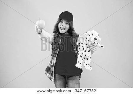 Reduce stress. Girl little fashionable schoolgirl with backpack carry soft toy dog and hold apple. Healthy lifestyle. Mental and physical wellbeing. Schoolgirl daily life. Stylish schoolgirl. stock photo