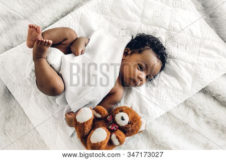 Portrait of cute adorable little african american baby sleep in a white bedroom stock photo