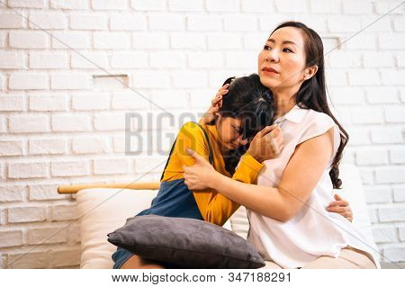 Asian mother comforting crying teenage daughter in miserable, stressed, depressed, sad state of mind. 40s Mom is hugging this adolescent teenager shoulders at indoors room. stock photo