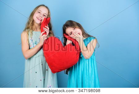Sisterhood concept. Valentines day. Friendly relations siblings. Family love. Happy feeling love. Loving sister. Sincere kids share tenderness and love. Girls hug red plush heart toy symbol love stock photo