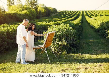 Beautiful adult couple drawing in a summer field stock photo