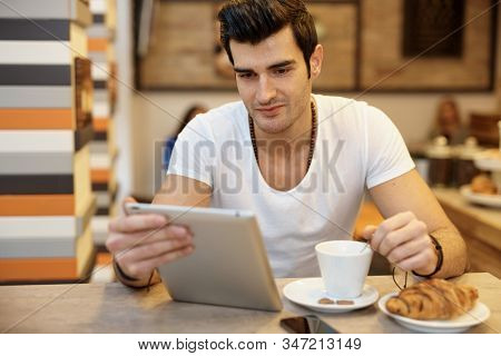 Young man using tablet computer in cafeteria. stock photo
