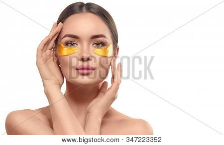 Woman with under eye collagen gold pads, beauty model girl face with healthy fresh skin. Skin care concept, anti-aging moisturizing eye mask, golden hydrogel patches, eye skin treatment, cosmetology stock photo