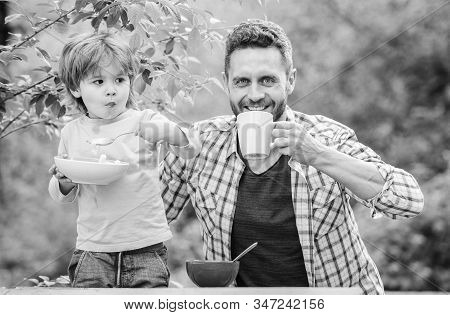 Healthy eating for both of us. healthy food and dieting. happy fathers day. Little boy with dad eat cereal. Morning breakfast. son and father eating outdoor. Family bonds. Enjoying time together stock photo