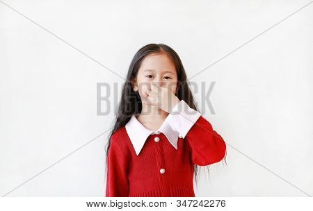 Adorable Asian little child girl gesture squeezing nose with fingers isolated over white background. stock photo