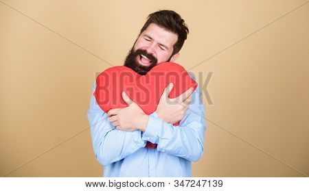 Happy in love. Make him feel loved every day. Man bearded hipster hug heart. Celebrate valentines day. Guy with beard and mustache in love romantic mood. Feeling love. Dating and relations concept stock photo