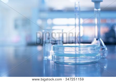 glass plate and beaker flask in analysis medical science blue laboratory background stock photo