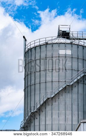 Agricultural silo at feed mill factory. Big tank for store grain in feed manufacturing. Seed stock tower for animal feed production. Commercial feed for livestock, swine and fish industries. stock photo