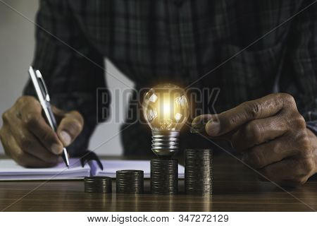 Business man putting coin with light bulb on table for saving bank and account for his money all in finance accounting concept. stock photo