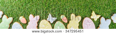 Sweet Easter baking cooking background with traditional Easter bunny and egg cookies, sugar sprinkles, Spring green grass background copy space layout stock photo