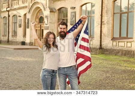 American citizenship is a very precious possession. Bearded man and sensual woman holding american flag on July 4th. American couple celebrating Independence day. Living the American dream. stock photo
