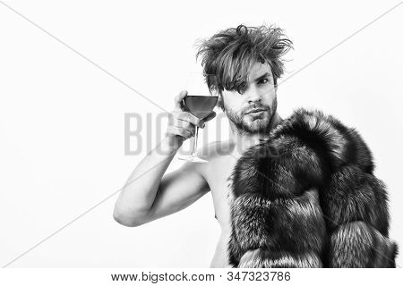 Rich athlete enjoy his life. Sexy sleepy rich macho tousled hair drink wine isolated on white. Health and wellbeing. Richness and luxury concept. Guy attractive rich posing fur coat on naked body stock photo