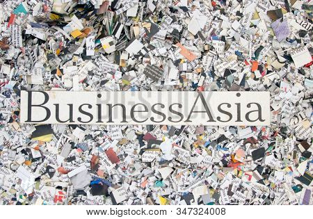 Newspaper confetti from above with the words Business Asia background stock photo