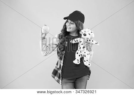 Healthy lifestyle. Stylish schoolgirl. Reduce stress. Girl little fashionable schoolgirl with backpack carry soft toy dog and hold apple. Mental and physical wellbeing. Schoolgirl daily life. stock photo