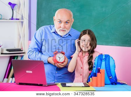 Little girl man tutor study. Time to study. Beginning of lesson. Study online lesson. Pedagogue friendly kind. Punctual pedagogue. Back to school. Teacher help schoolgirl. Study digital science stock photo