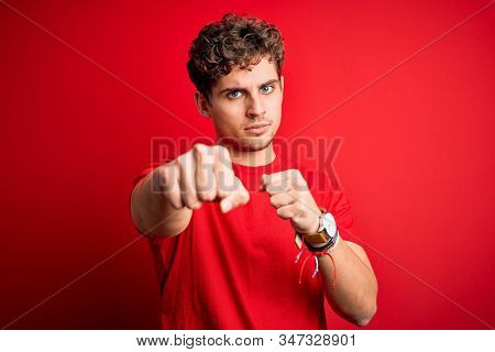 Young blond handsome man with curly hair wearing casual t-shirt over red background Punching fist to fight, aggressive and angry attack, threat and violence stock photo