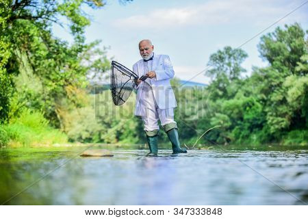 i am retired. fisher celebrate retirement. good production. retired businessman. Good profit. hobby and recreation. Fishermen in formal suit. successful catch. business success. mature man fishing stock photo