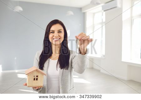 Realtor agent is a realtor with keys in hand against the background of a white real estate room apartment home. stock photo