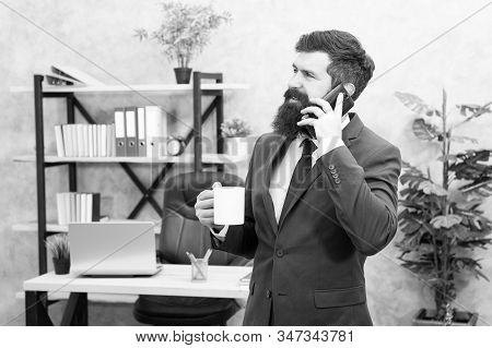 Coffee is pledge of successful negotiations. Caffeine addicted. Man bearded businessman hold cup and smartphone. Mobile call. Start day with coffee. Coffee relaxing break. Boss enjoying energy drink. stock photo