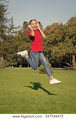 Active and dynamic. Active child jump over green grass. Happy little girl move active to music. Energetic small kid listen to music in earphones. Active and happy. Summer vacation. stock photo
