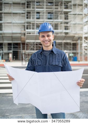 Smiling site manager reading a blueprint in front of a construction site stock photo