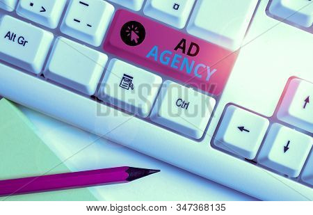 Conceptual hand writing showing Ad Agency. Business photo text business dedicated to creating planning and handling advertising White pc keyboard with note paper above the white background. stock photo