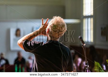 Rear view of male with blonde hair performing by microphone stand on stage in front of audience at auditorium hall during event festival stock photo