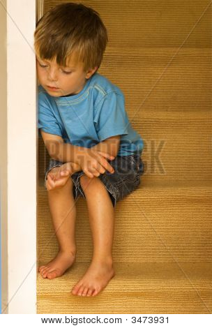 Impression of a neglected child sitting on carpeted stairway. stock photo
