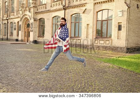 Patriotic spirit. Patriotic man jumping with american flag. Independence day. Bearded hipster patriotic citizen. Happy and proud. Join celebration. Patriotic guy expressing happiness in street. stock photo
