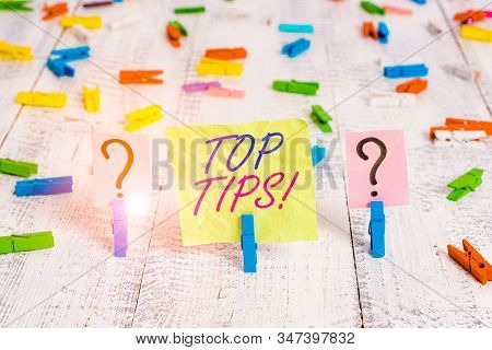 Word writing text Top Tips. Business concept for small but particularly useful piece of practical advice Scribbled and crumbling sheet with paper clips placed on the wooden table. stock photo