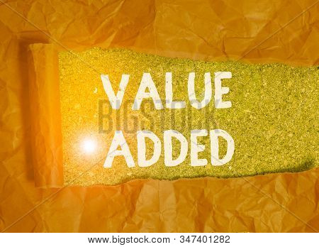 Handwriting text Value Added. Concept meaning the extra value created over and above the original value Cardboard which is torn in the middle placed above a wooden classic table. stock photo