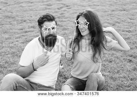 Photo booth party for lovers. Romantic couple smiling with happy party look on green grass. Happy girlfriend and boyfriend holding party props on stick. Enjoying party fun. stock photo