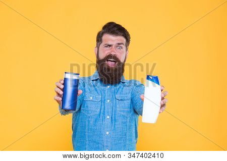 Versatile hygiene products for sale. Bearded man hold cosmetic products. Hipster presenting beard hair and skin products. Product promotion. Bottles for advertising text, copy space. stock photo