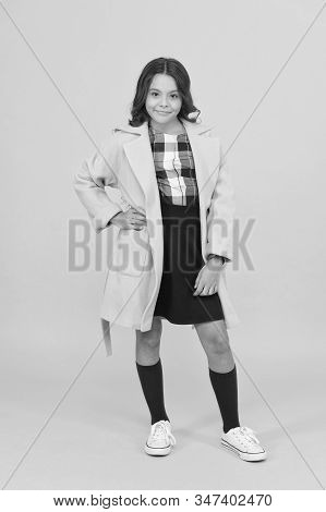 Keep her warm and stylish. Stylish girl in formal coat go to school. Little child with stylish autumn look on yellow background. Stylish and comfortable. stock photo