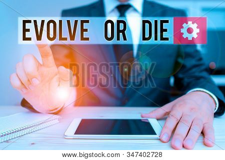 Word writing text Evolve Or Die. Business concept for Necessity of change grow adapt to continue living Survival Male human wear formal clothes present presentation use hi tech smartphone. stock photo
