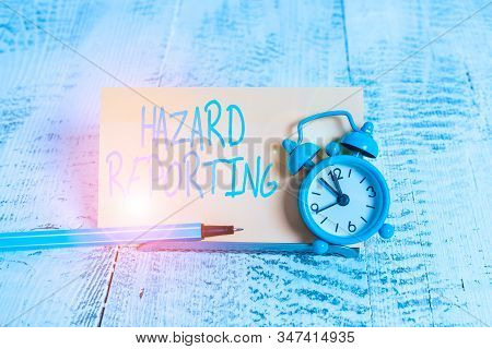 Handwriting text Hazard Reporting. Concept meaning account or statement describing the danger or risk Mini blue alarm clock stand tilted above buffer wire in front of notepaper. stock photo