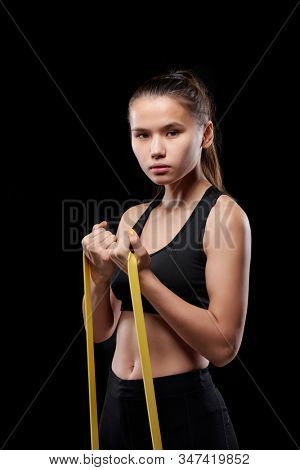 Pretty young fit female in activewear exercising with resistance band in front of camera over black background in isolation stock photo