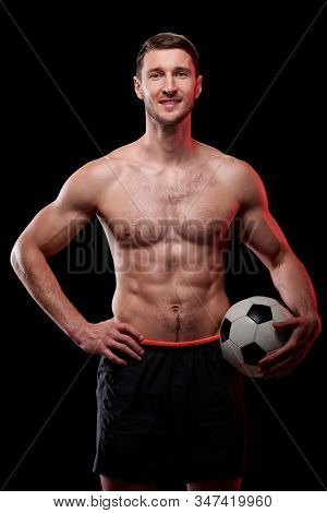 Happy muscular shirtless footballer with ball standing in front of camera against black background in isolation stock photo