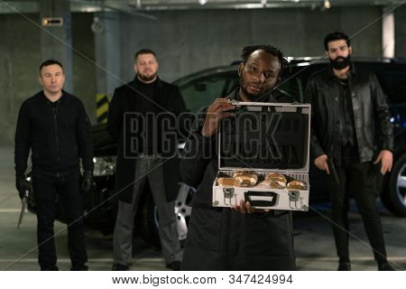 Young African gangster or drug dealer holding open suitcase full of drugs with his armed gang on background stock photo