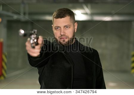 Young killer or agent in black jacket and t-shirt directing handgun on victim or criminal ready to shoot stock photo