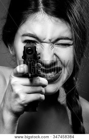 serious young woman with gun aiming at camera, grimacing, closeup portrait, monochrome stock photo